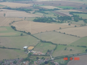 The view from the village centre towards the Grange and Abbey Farm hidden amongst the trees, near centre, with Northampton Road bottom right and New Row bottom centre.