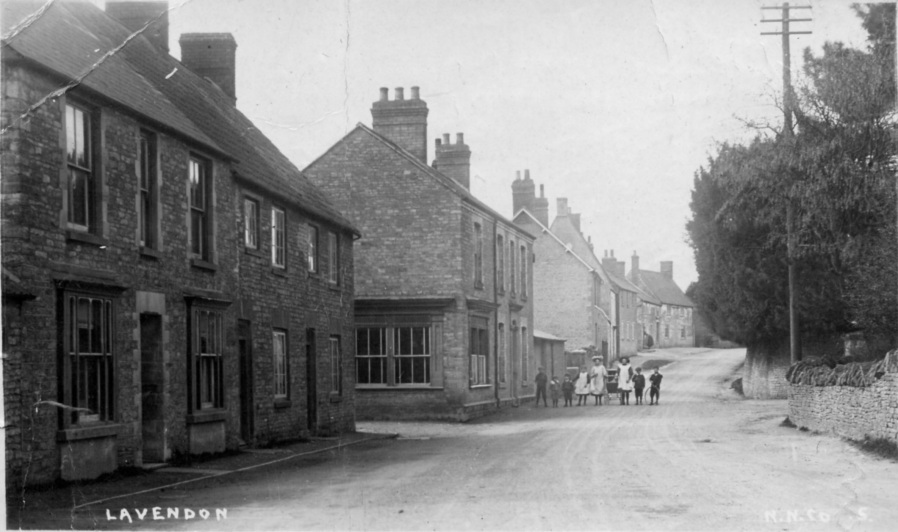 Northampton Road, Lavendon, with the former butcher's shop to the left of the pedestrians.